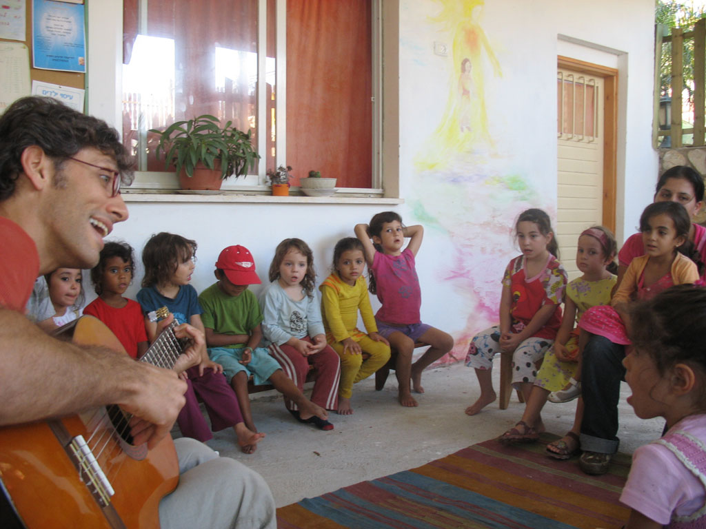 Amir singing with the children of Ein Bustan